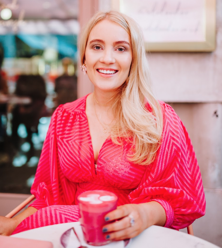 Millie Poppins wearing a pink shirt sitting in a coffee shop drinking a pink latte